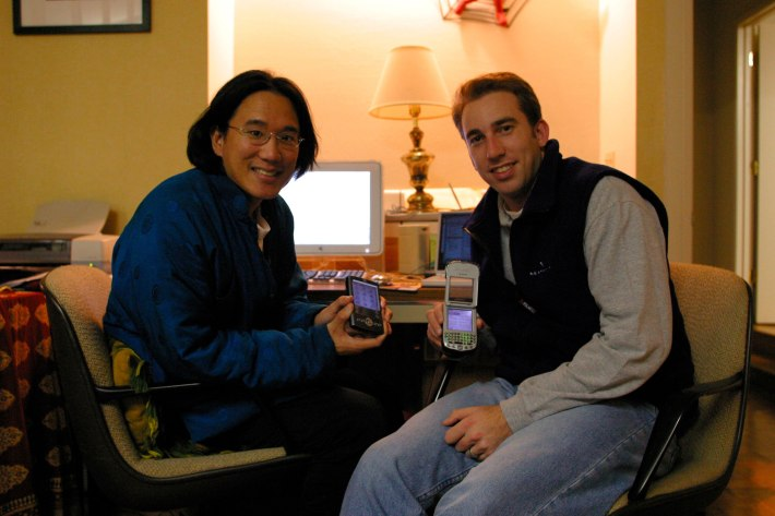 Holding up old Palm and Handspring devices in Cupertino on January 23, 2003. The one Alex is displaying is actually a phone!